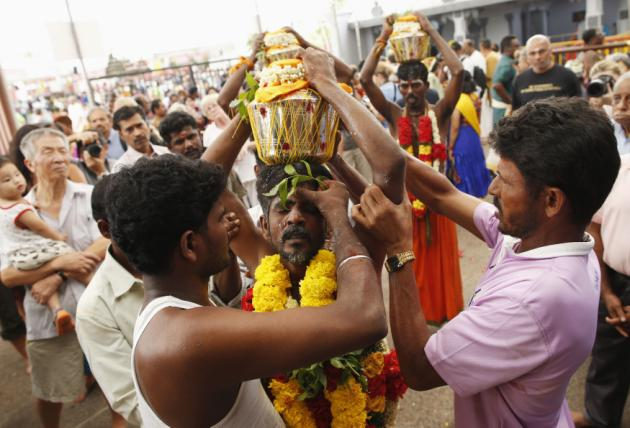 A devotee falls into a trance as he carries a milk pot over his head during Thaipusam festival in Singapore