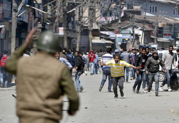 Kashmiri protesters run towards Indian security personnel during a demonstration against the plan to resettle Hindus in Srinagar